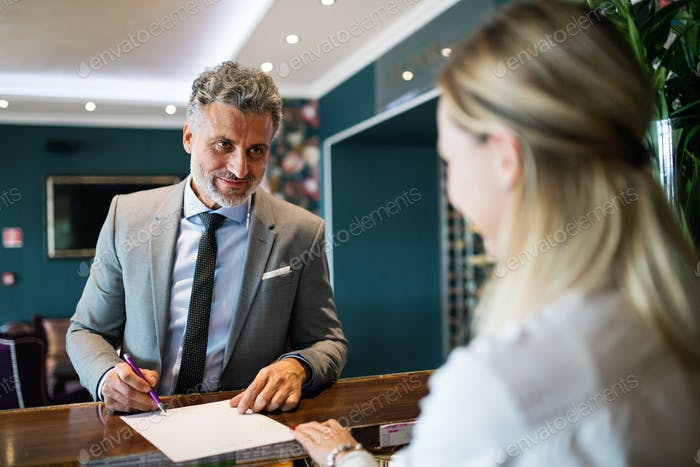 Reife Geschäftsmann an der Hotelrezeption.