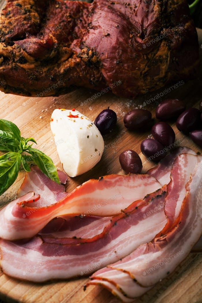 Geräucherter Speck mit Brot, Mozzarella, Oliven und Basilikum