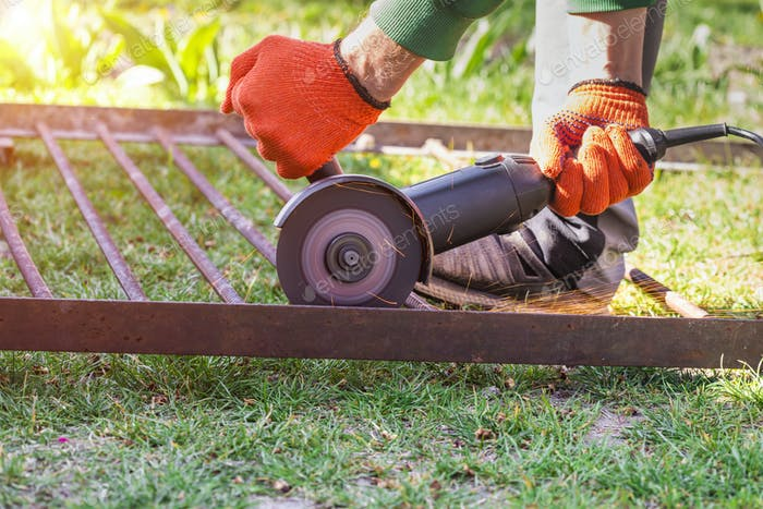 Worker using angle grinder in garden and throwing sparks