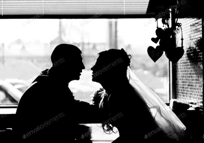 Silhouette of loving couple in the cafe