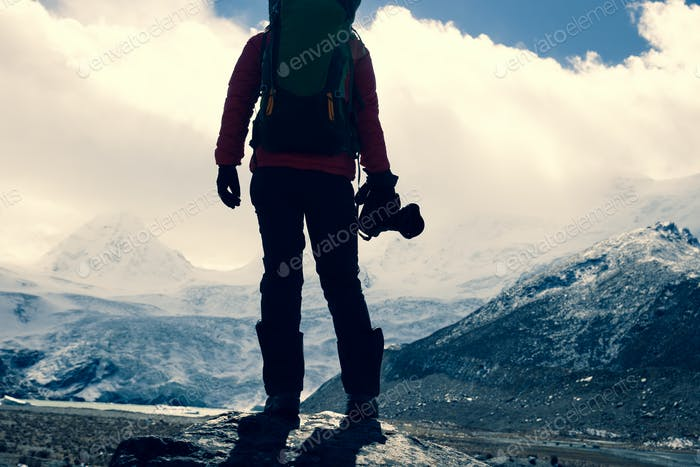 HikingWoman hiker with camera in winter high altitude mountains
