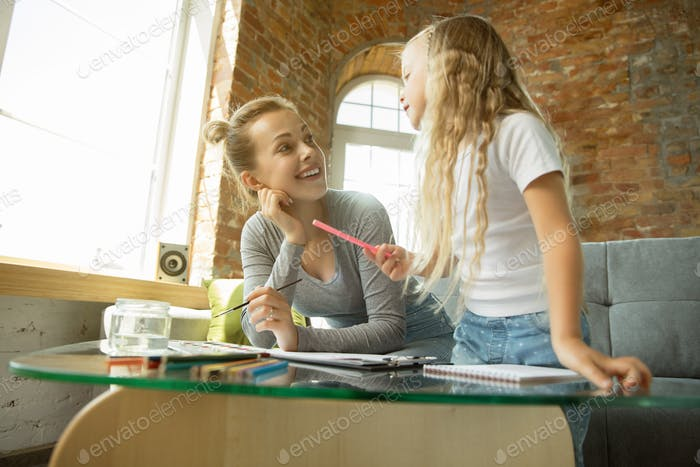 Teacher and little girl, or mom and daughter. Homeschooling concept