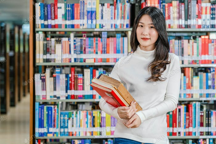 Portrait Asian young Student in casual suit standing and holding the book at book shelf