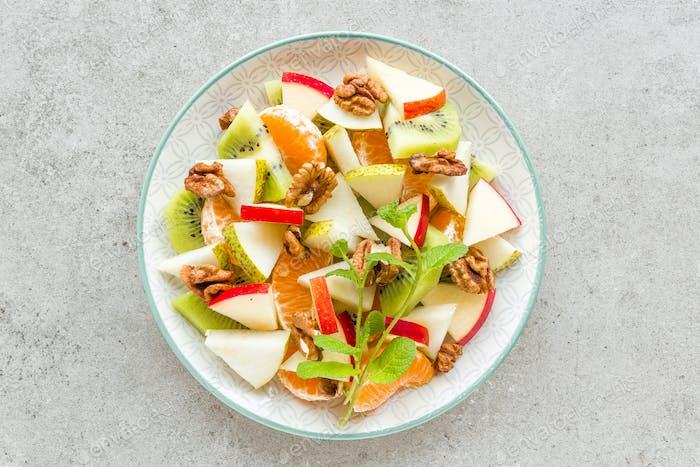 Obstsalat aus frischem süßem Apfel, Birne, Mandarine und Walnüssen. Gesundes vegetarisches Essen