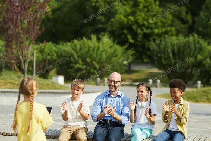 Kinder applaudieren niedlichen Mädchen im Freien Lektion