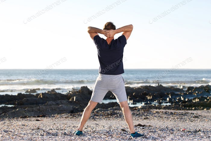 back of sports man looking at sea