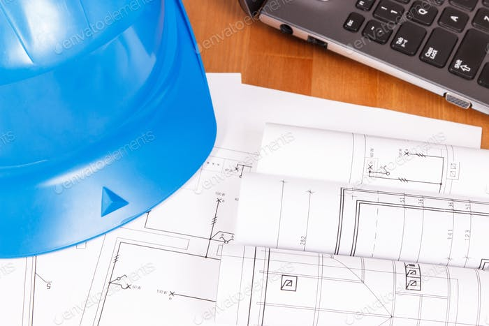 Electrical blueprints or diagrams with laptop and protective blue helmet, technology concept
