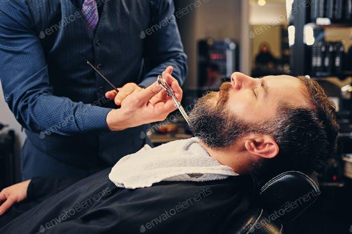 Крупным планом изображение парикмахера делает бороду вырезать человека.