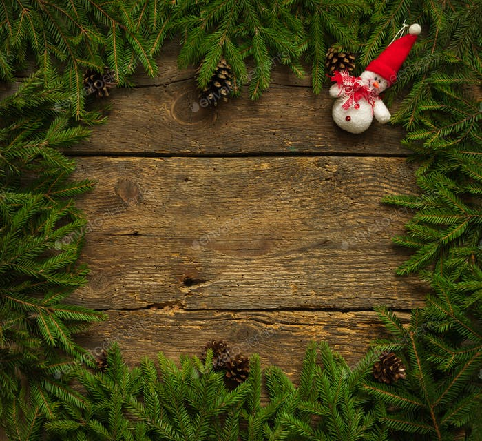 Christmas tree branches with snowman on wooden texture