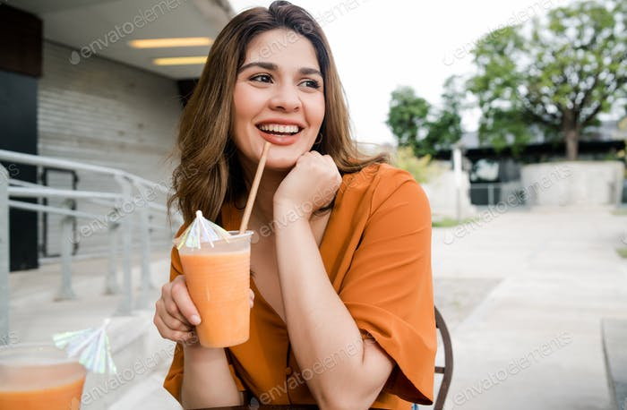 Woman drinking fresh fruit juice outdoors.