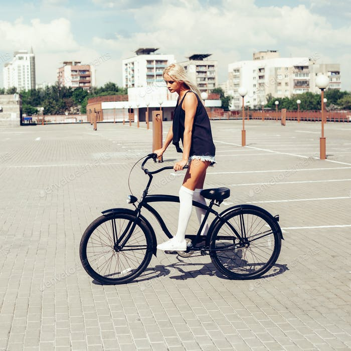 beautiful blonde head woman on bike in city