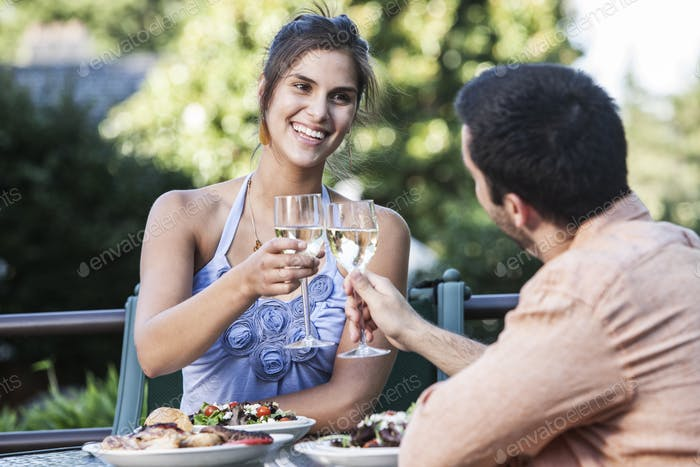 HIspanic couple having a healthy meal and a glass of white wine.