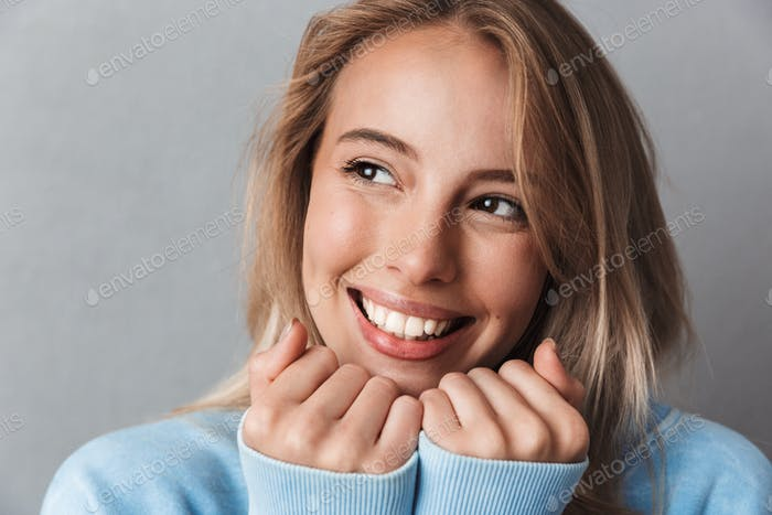 Close up of a cheerful young girl in blue sweatshirt