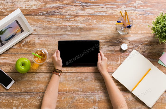 hands with tablet pc and notebook at office table