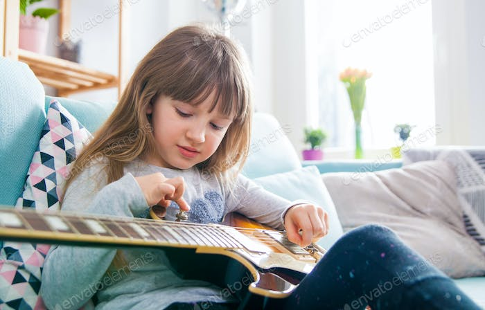 Cute little girl playing guitar at home