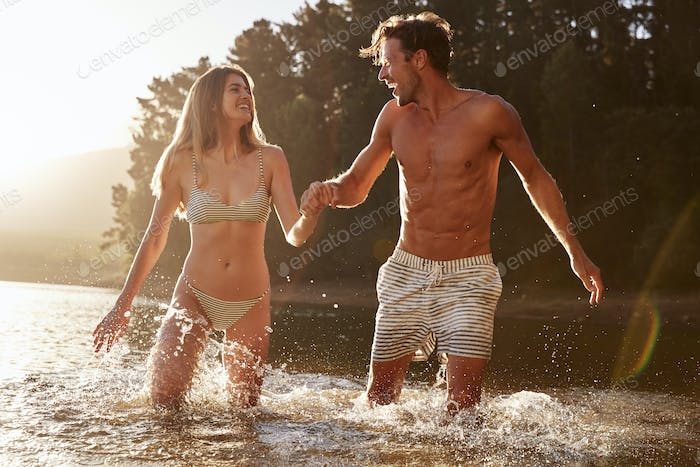 Young white couple smiling at each other standing in a lake