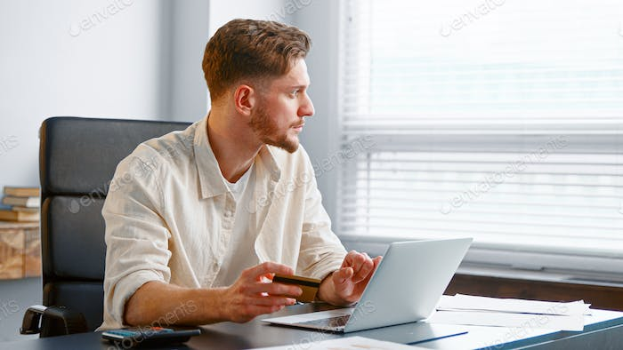 Young man with beard pays online holding credit card