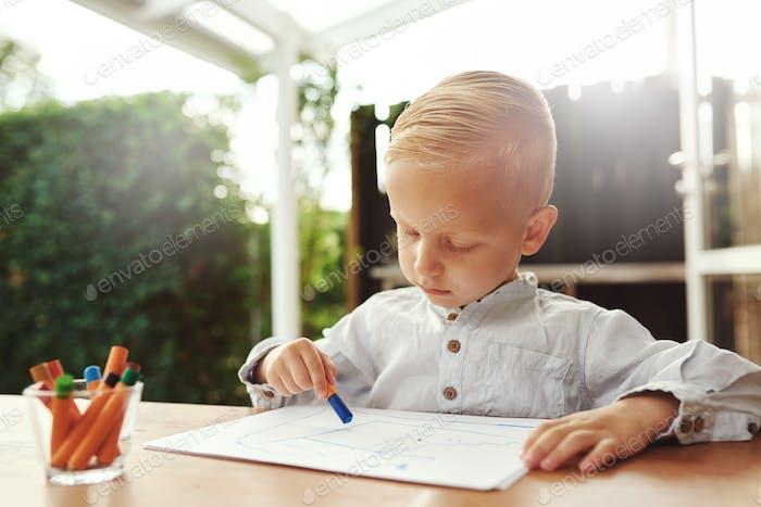 Kleiner blond Junge stehend Zeichnung mit Buntstiften