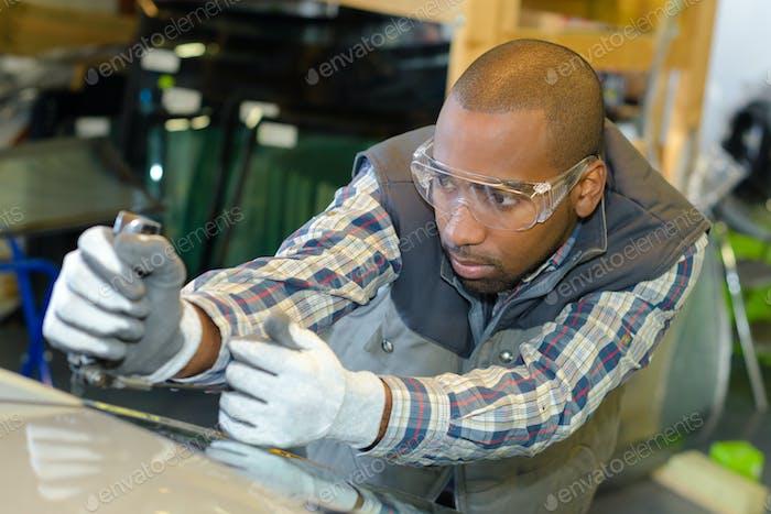 Garage worker fitting windscreen