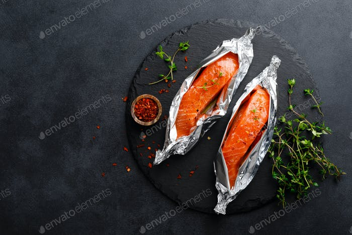 Rohes Lachsfischfilet in Folie auf schwarzem Hintergrund