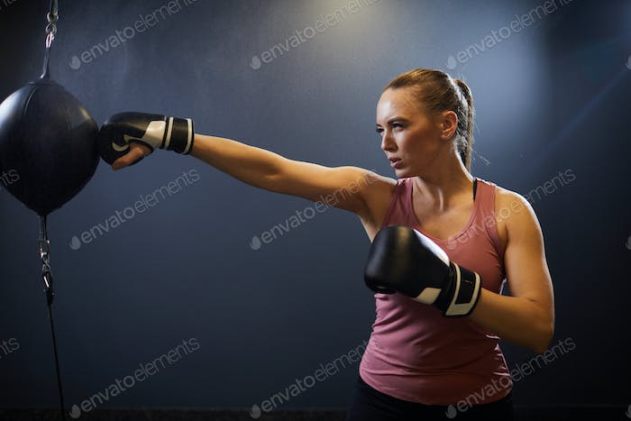 Strong Young Woman Boxing on Black