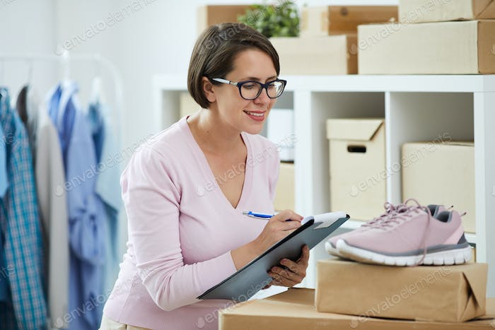 Young woman writing down name and number of new pink sneakers