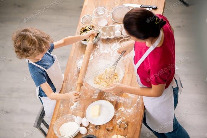Little boy holding rolling-pin over wooden table while his mother making dough
