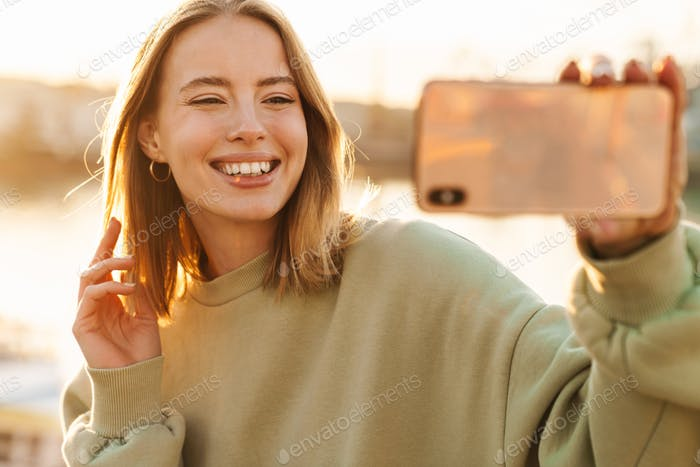 Portrait of cheerful woman taking selfie on cellphone while walking