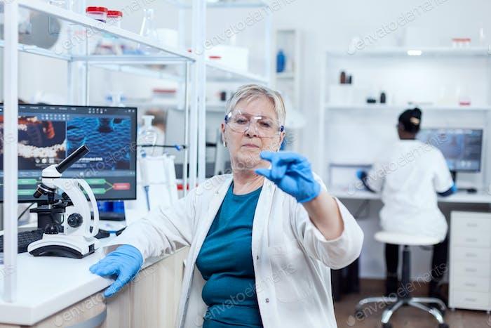 Senior scientist in modern laboratory holding genetic sample