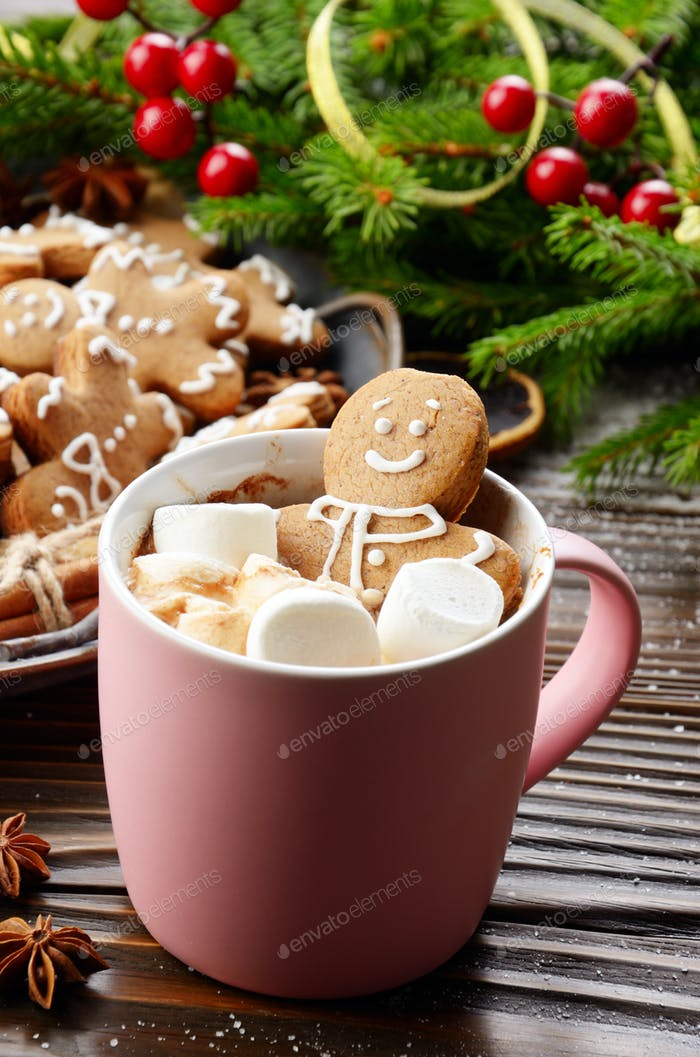 Pink mug with hot chocolate marshmallows and gingerbread man on