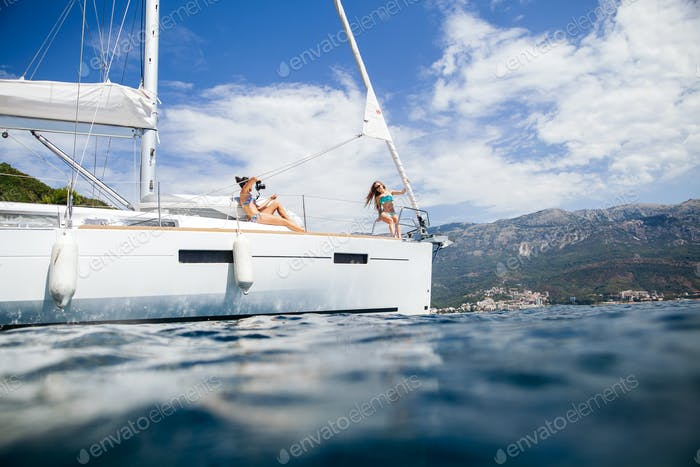 women relax on yacht