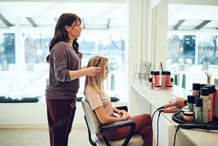 Young hairdresser styling a female client's hair in her salon