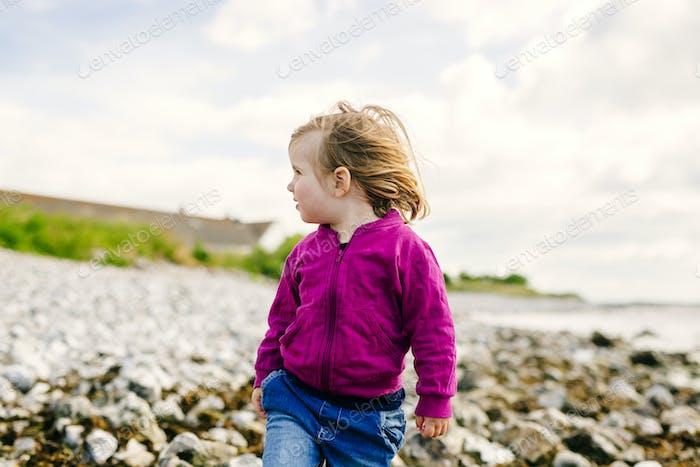 Girl walking on beach against cloudy sky