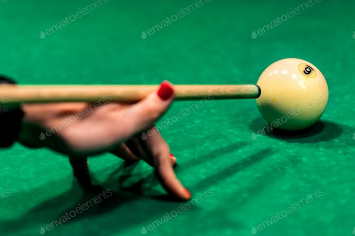 Woman's hand with cue playing pool
