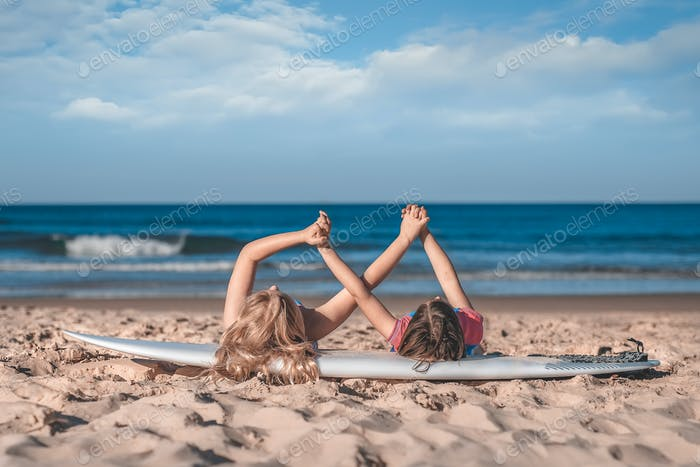 Two little girls' hands holding together laying on a surfboard on the sandy ocean beach.