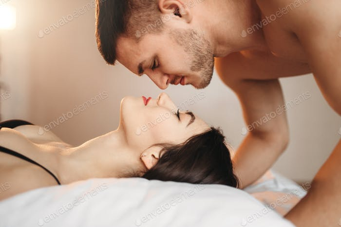 Love couple lies on big white bed, sex romance