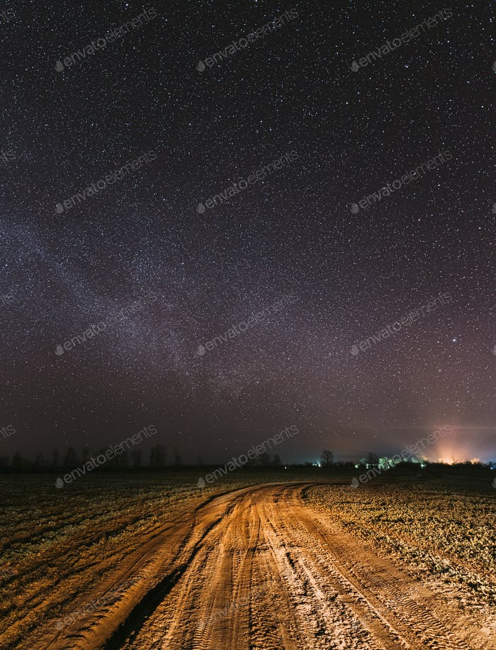Night Starry Sky With Glowing Stars Above Countryside Road Landscape. Milky Way Galaxy And Rural