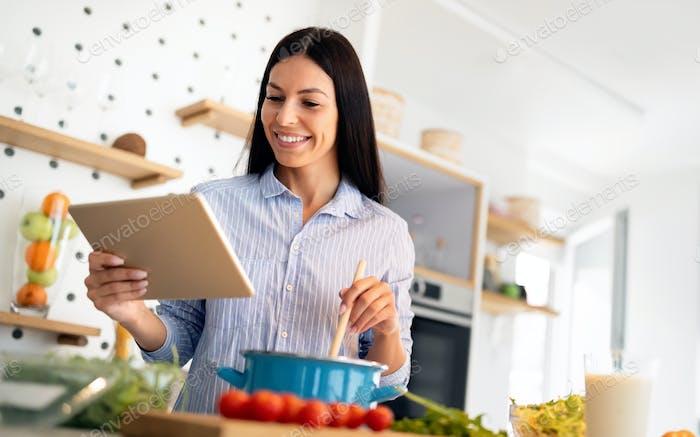 Cocinar mujer mirando la computadora mientras se prepara la comida en la cocina