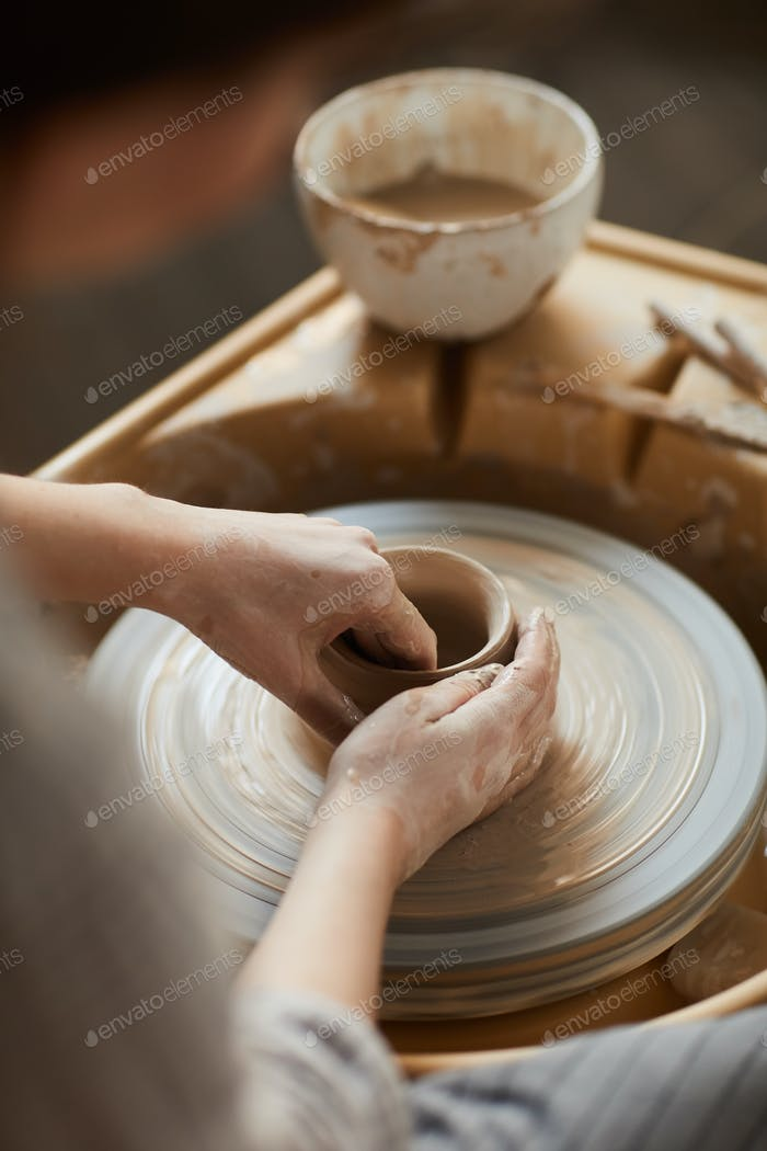 Shaping clay on pottery wheel