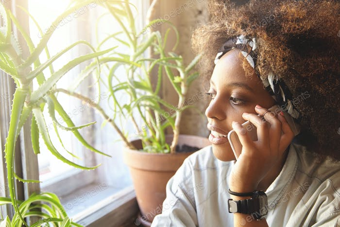 People, technology and communication concept. Cute fashionable dark-skinned woman with Afro hairctyl