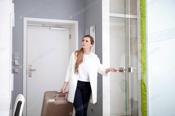 Mujer tirando de la maleta en la habitación de hotel moderna