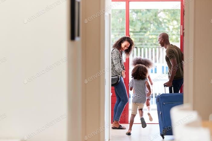 Familia de pie junto a Puerta con maleta a punto de salir de vacaciones