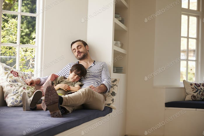 Father And Son Sleeping On Window Seat At Home Together