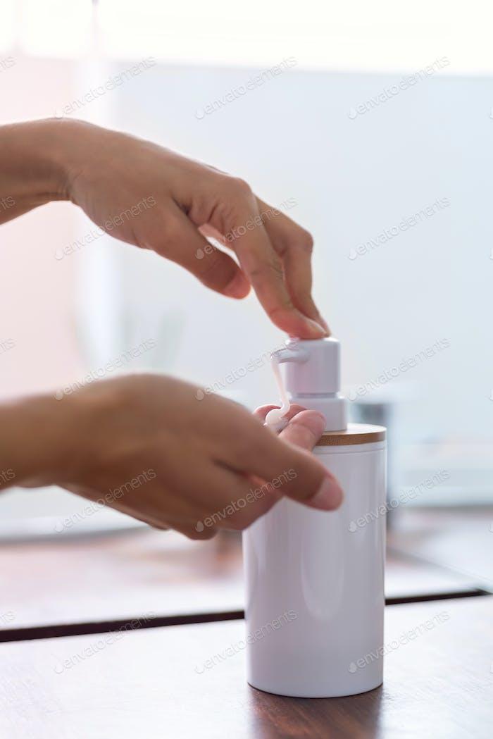 Detail der Hände der Frau mit Seife und Waschen der Hände unter dem Wasserhahn