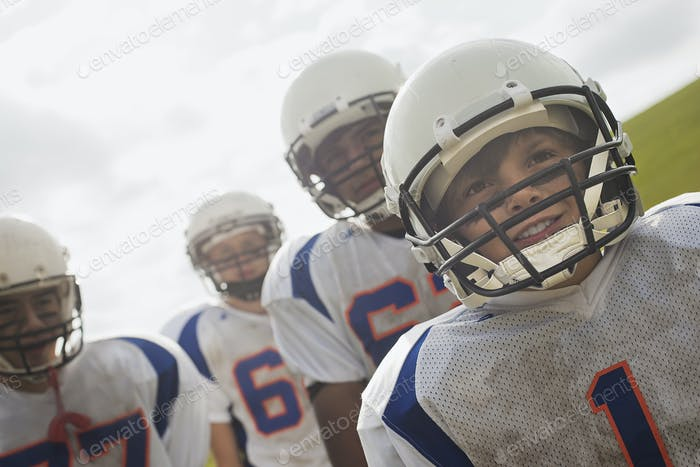A group of young football players in sports uniform and protective helmets.