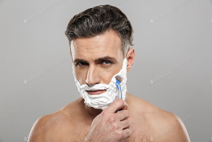 Mature man shaving with razor.