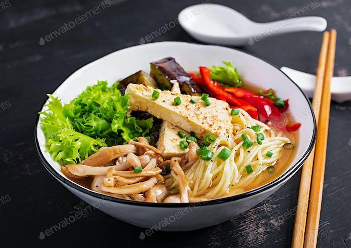 Asiatische vegane Nudelsuppe mit Tofu-Käse, Shimeji Pilzen und gebratenen Auberginen