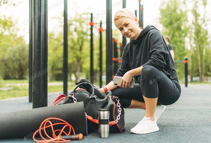 Attraktive Passform junge blonde Frau in schwarz Sport tragen gehen, um auf Straße Workout-Bereich trainieren