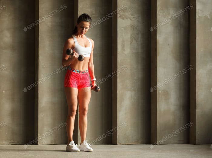 sportswoman doing biceps curls with dumbbells