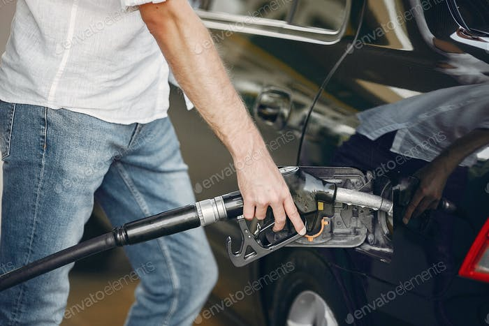Handsome man pours gasoline into tank of car